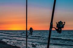 Puesta del sol detrás de las cañas de pescar en un mar Imágenes de archivo libres de regalías