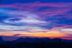 Puesta del sol detrás de las montañas y de la luz crepuscular en el cielo Fotografía de archivo libre de regalías