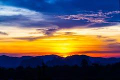 Puesta del sol detrás de las montañas y del crepúsculo Foto de archivo libre de regalías