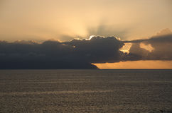 Puesta del sol detrás de las nubes Foto de archivo libre de regalías