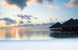 Puesta del sol detrás de las nubes y de la silueta de chozas en la playa Fotos de archivo libres de regalías