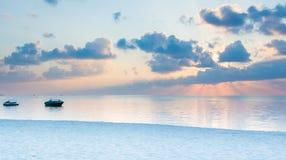 Puesta del sol detrás de las nubes y de los barcos en la playa Imagenes de archivo
