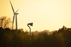Puesta del sol detrás de las turbinas de viento Foto de archivo libre de regalías