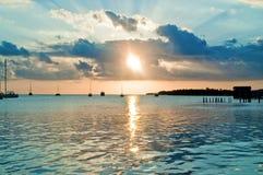 Puesta del sol detrás de los barcos de vela Imagen de archivo