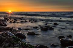 Puesta del sol detrás de piedras en un mar Fotografía de archivo libre de regalías