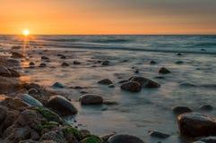 Puesta del sol detrás de piedras en un mar Imágenes de archivo libres de regalías