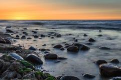Puesta del sol detrás de piedras en un mar Imagen de archivo