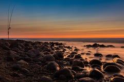 Puesta del sol detrás de piedras y de cañas de pescar en un mar Foto de archivo libre de regalías