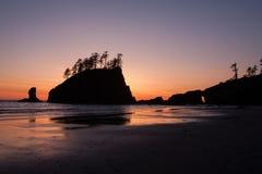 Puesta del sol detrás de pilas del mar Imágenes de archivo libres de regalías