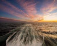 Puesta del sol detrás de un barco de cruceros que cruza en el mar Fotografía de archivo