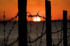 Puesta del sol detrás del alambre de púas, Foto de archivo