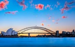 Puesta del sol detrás del teatro de la ópera y de Sydney Harbour Bridge Imagen de archivo libre de regalías