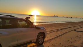 Puesta del sol detrás del vehículo parqueado en la playa Imagen de archivo