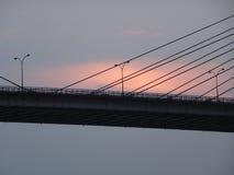 Puesta del sol detrás del puente Foto de archivo libre de regalías