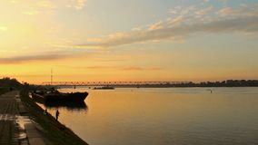 Puesta del sol detrás del puente y opinión sobre un río Danubio y un pescador almacen de video
