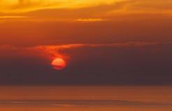 Puesta del sol detrás de las nubes en Oia Imagen de archivo