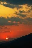 Puesta del sol distante sobre siluetas de crestas de colinas imágenes de archivo libres de regalías
