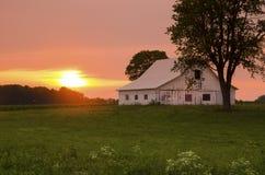 Puesta del sol divina sobre granero Fotos de archivo libres de regalías