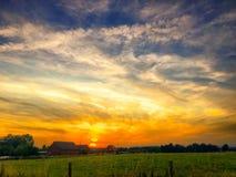 Puesta del sol dramática hermosa sobre un campo Imagen de archivo libre de regalías