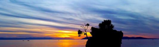 Puesta del sol dramática sobre el mar adriático con Kamen Brela - isla famosa minúscula en Brela Imágenes de archivo libres de regalías