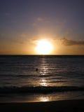 Puesta del sol dramática a través de las nubes y reflejo en el Pacífico Fotos de archivo