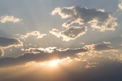 Puesta del sol - el sol a través de las nubes Fotos de archivo libres de regalías
