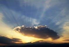 Puesta del sol - el sol a través de las nubes Imágenes de archivo libres de regalías