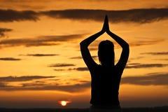 Puesta del sol, ella meditating. Foto de archivo libre de regalías