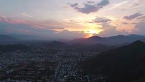 Puesta del sol en Asia en el fondo de la ciudad, del mar y de las montañas almacen de metraje de vídeo