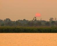 Puesta del sol en bosque cerca del pequeño río en Tailandia Foto de archivo
