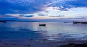 Puesta del sol en colores pastel con el barco Imagenes de archivo