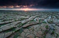 Puesta del sol en costa de mar de Wadden durante la bajamar Fotografía de archivo