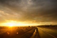 Puesta del sol en el camino mojado Imagen de archivo libre de regalías