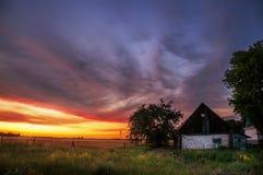 Puesta del sol en el campo Cielo increíblemente hermoso con nubes rojas y una pequeña casa rural Imagen de archivo