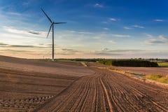 Puesta del sol en el campo marrón, el cielo azul y la turbina de viento, Polonia fotografía de archivo