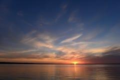Puesta del sol en el cielo azul claro del verano sobre el lago Fotos de archivo libres de regalías