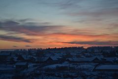 Puesta del sol en el cielo sobre el pueblo ruso del invierno imagenes de archivo