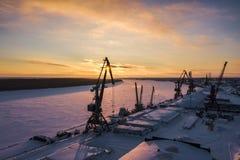 Puesta del sol en el fondo de las grúas portuarias y del río congelado foto de archivo