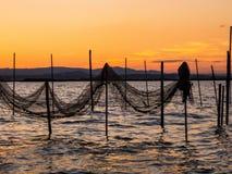 Puesta del sol en el lago en Albufera, España, redes de pesca imagen de archivo