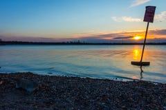 Puesta del sol en el lago con el cielo azul Foto de archivo