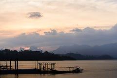 Puesta del sol en el lago con el hombre y el barco de Siluate Imagen de archivo libre de regalías