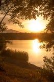 Puesta del sol en el lago con las siluetas de árboles Imágenes de archivo libres de regalías
