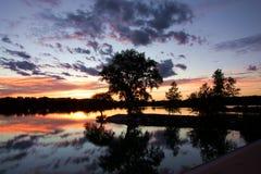Puesta del sol en el lago con los árboles silueteados Fotos de archivo