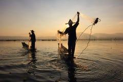 Puesta del sol en el lago con los pescadores Fotos de archivo libres de regalías