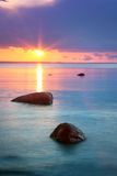 Puesta del sol en el mar con agua y las nubes hermosas Imagen de archivo libre de regalías