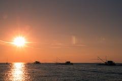 Puesta del sol en el mar con alguna casa en el agua Foto de archivo libre de regalías