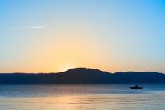 Puesta del sol en el mar con el barco en agua fotos de archivo