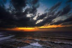 Puesta del sol en el mar con el mar agitado Fotografía de archivo libre de regalías