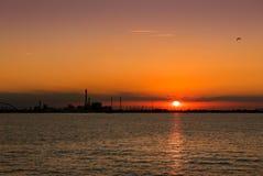 Puesta del sol en el mar con la silueta de un eje industrial químico Fotografía de archivo libre de regalías