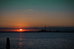 Puesta del sol en el mar con la silueta de un eje industrial químico Imágenes de archivo libres de regalías